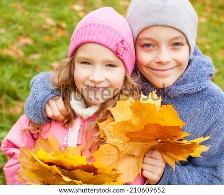 Children at autumn. Girls and boy outdoors - stock photo