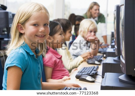 Children at computer terminals with teacher in background (depth of field/high key)