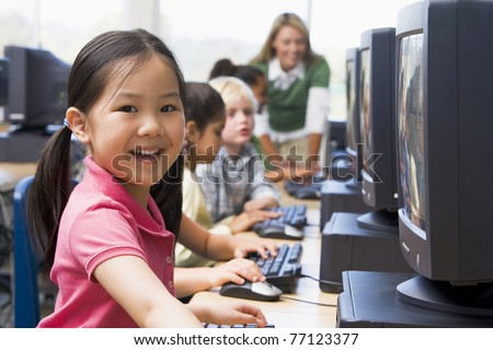 Children at computer terminals with teacher in background (depth of field/high key) - stock photo