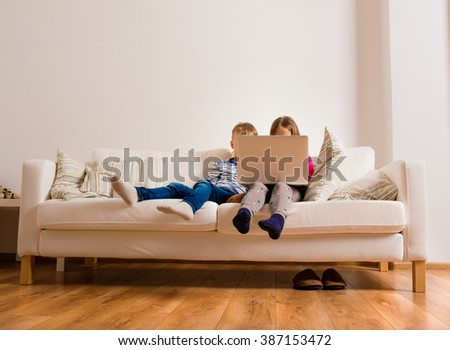 Children at home sitting on sofa, playing with laptop - stock photo