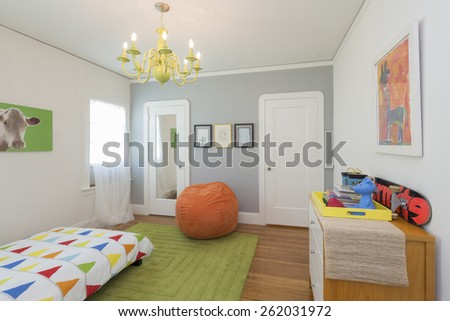 Children bedroom / kids room with colorful decoration, green rug, bed, chandelier and modern chest. - stock photo