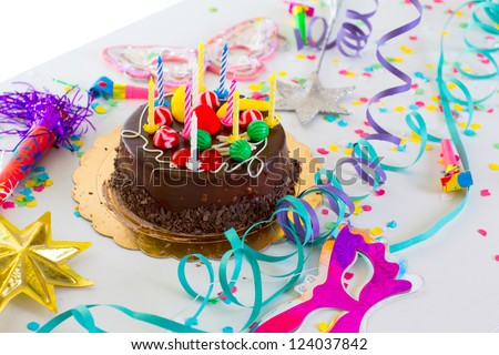 Children birthday party with chocolate cake confetti garland and serpentine - stock photo