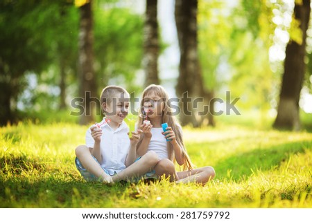Children blowing bubbles in the summer park