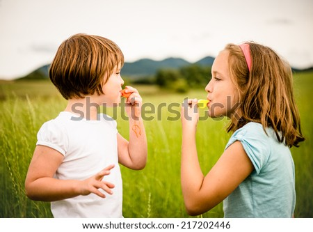 Children blowing on each other in whistles - outdoor in nature - stock photo
