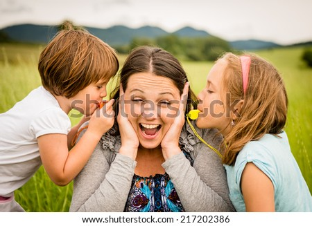 Children blowing whistles to mother's ears- outdoor in nature - stock photo