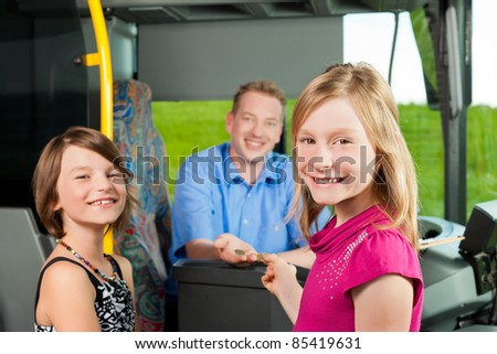 Children boarding a bus and buying a ticket