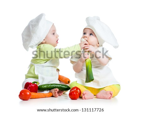 children boy and girl wearing a chef hat with healthy  food vegetables - stock photo