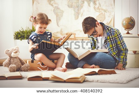 children brother and sister, boy and girl reading a book at home - stock photo