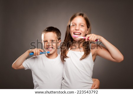 children brushing her teeth on a gray background - stock photo