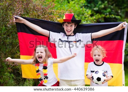 Children cheering and supporting German national football team. Kids fans and supporters of Germany during soccer championship. Family with teenager boy, little girl and baby watch football game