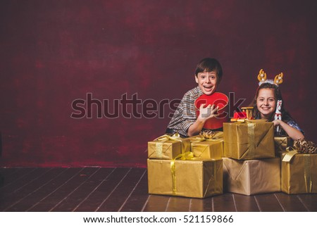 Children Christmas. Children of the new year. Children and lots of Christmas gifts on a blank wall. Children and gift boxes. Boy and girl with Christmas presents