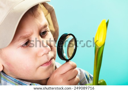 Children development. Child examining flower looking through a magnifying glass. Environmental awareness education. - stock photo