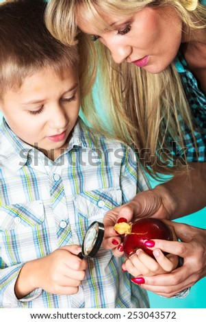 Children development concept. Mother with son little boy examining apple looking through a magnifying glass. - stock photo
