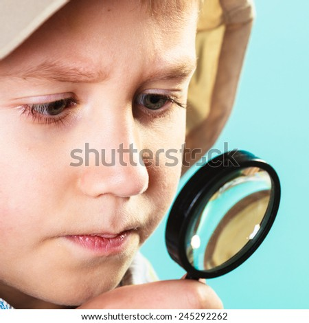 Children development, education concept. Child looking through a magnifying glass loop, closeup - stock photo