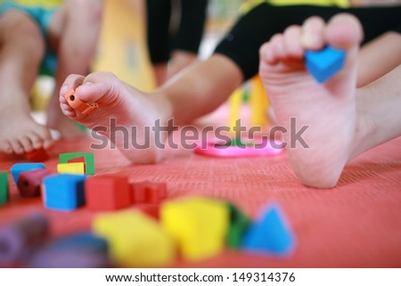 children do improving massage of feet and develop a motility of fingers - stock photo