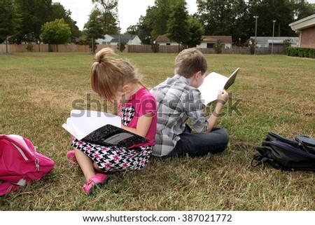 Children doing homework on schools front lawn. - stock photo