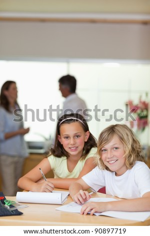 Children doing their homework with their parents behind them - stock photo
