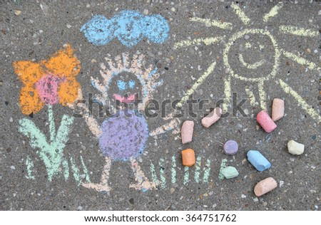 children drawing on a sidewalk made with chalk crayons - stock photo
