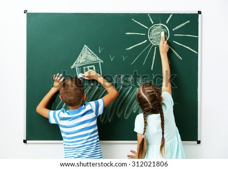 Children drawing on blackboard at school - stock photo