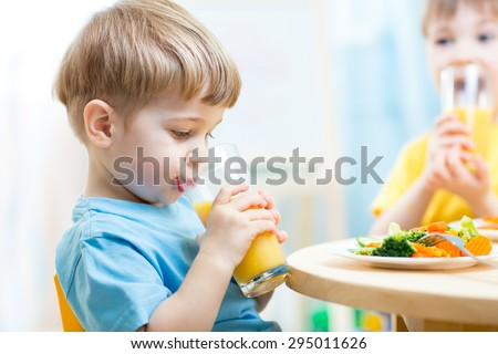 children drinking juice at nursery or at home - stock photo
