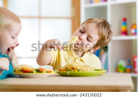 children eating healthy food in nursery or at home - stock photo