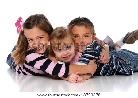 Children embracing laying on the floor over a white background