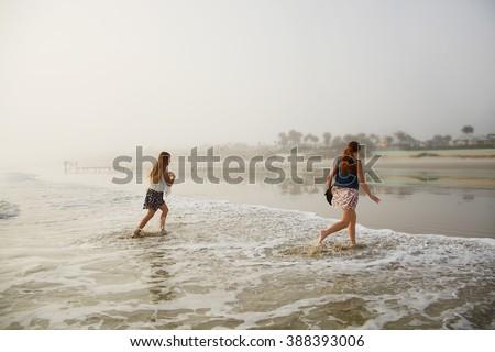 Children enjoying time on the beach on a foggy morning, Daytona Beach Florida, USA. - stock photo