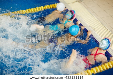 Children exercising in swimming pool - stock photo
