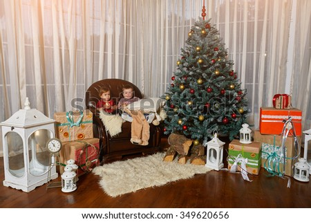 Children expect gifts near a Christmas tree - stock photo