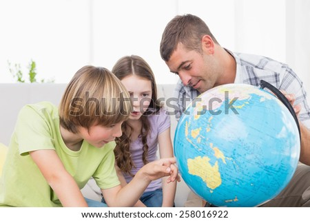 Children exploring globe while sitting with father in living room - stock photo