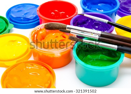 Children finger paint and paintbrushes closeup - stock photo