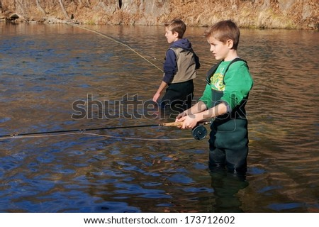 Children fishing - brothers and friends fly fishing in a clear stream  - stock photo