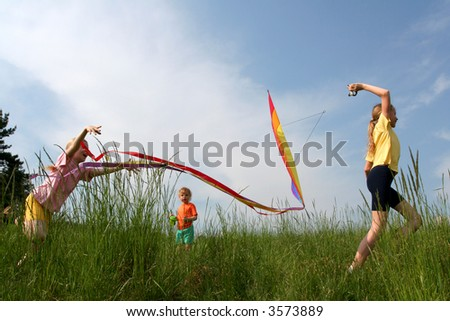 Children flying rainbow kite in the meadow on a blue sky background - stock photo