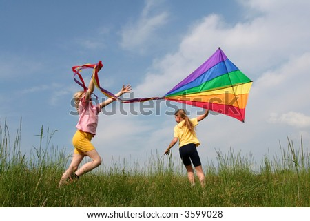 Children flying rainbow kite in the meadow on a blue sky background