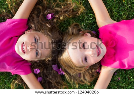 children friend girls lying together on garden grass smiling happy aerial view - stock photo