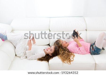 Children friends kid girls having fun playing with tablet pc lying on white sofa - stock photo