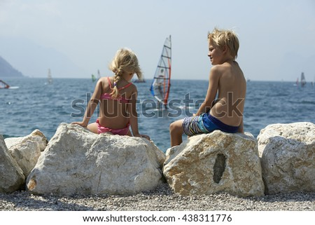 Children girl and boy sitting on the rock and enjoying the view of the lake Garda and looking at windsurfers. Lago di garda in summer Italy - stock photo