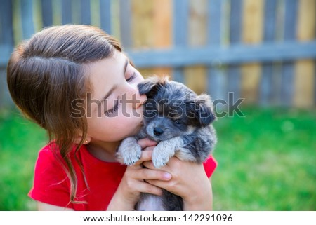 children girl kissing her puppy chihuahua doggy on the wood fence - stock photo