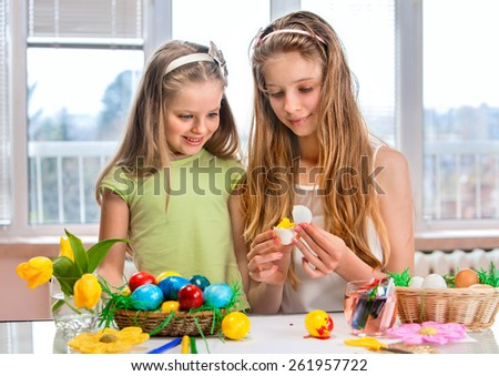 Children girl paint Easter eggs at home. Sibling. - stock photo