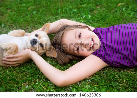 children girl playing with chihuahua dog lying on backyard lawn - stock photo