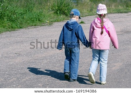 Children go on road, having joined hands - stock photo