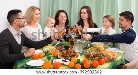Children, grandparents, and parents congratulating each other at home party - stock photo