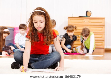 Children group drawing, a girl in red t-shirt sits in front - stock photo
