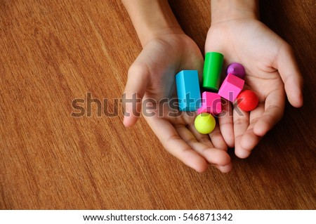 Children hand holding colorful of rubber cube and other shapes on wood texture background.