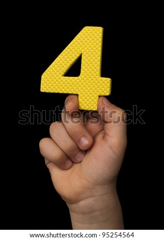Children hand holding the number Four. Black isolated yellow number Four - stock photo