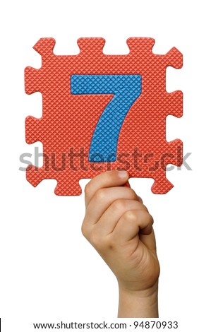 Children hand holding the number Seven. White isolated multicolor number Seven - stock photo