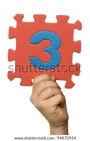 Children hand holding the number Three. White isolated multicolor number Three - stock photo