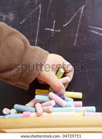 Children hand putting chalk to a blackboard - stock photo
