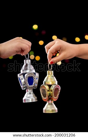 Children Hands Celebrating with Ramadan Lantern on Defocused Night Lights Background - stock photo