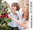 Children hanging Christmas decorations with their mother in the living-room - stock photo